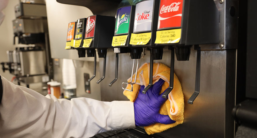 Wiping Soda Machine with Sanitizing Wipe