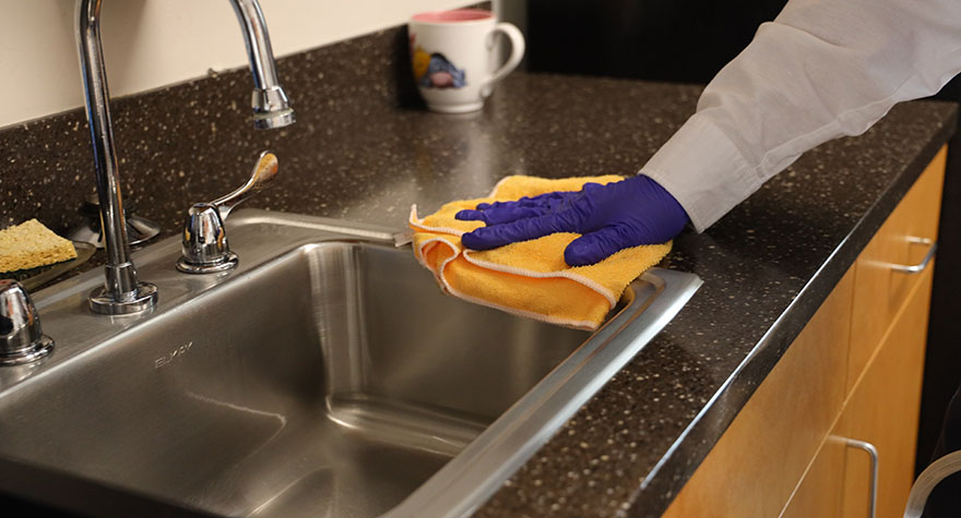 Wiping Kitchen Sink with Sanitizing Wipe